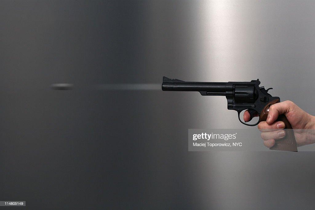 Hand holds discharging gun. : Stock Photo