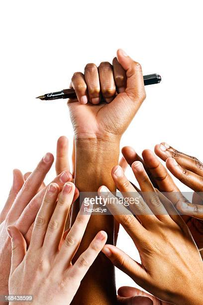 Hand holds fountain pen as many reach up for it