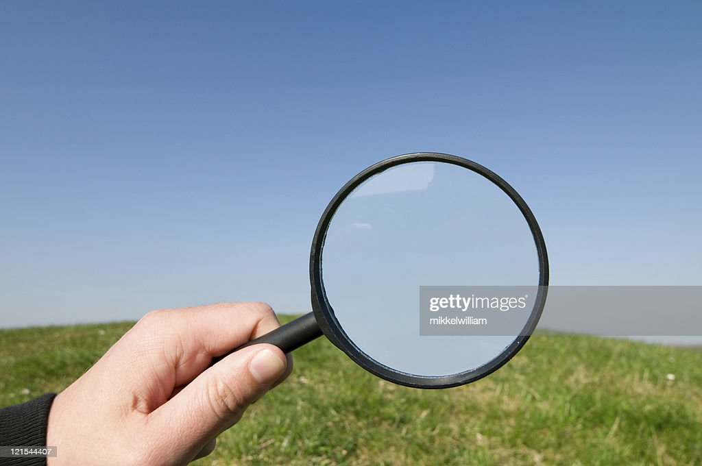 Hand holds magnifying glass up op a hill and sky : Stock Photo