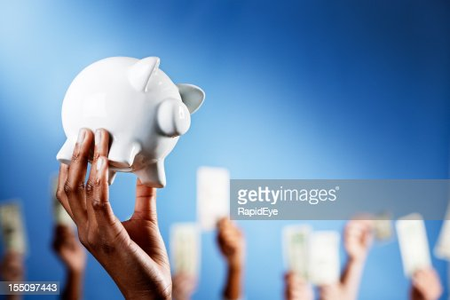 Hand holds piggy bank others in background wave money