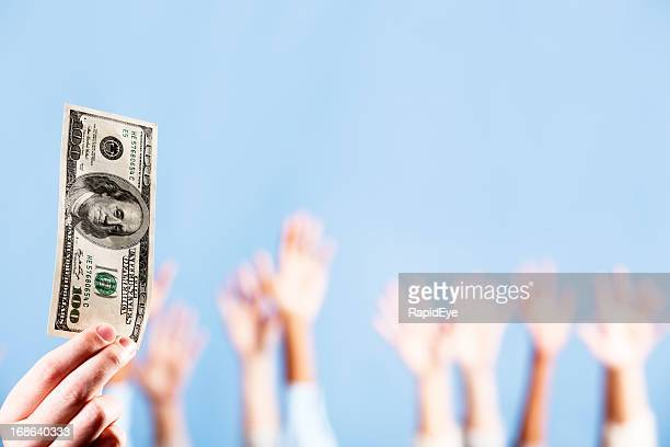 Hand holds up $100 bill; others raise hands in background