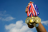 Hand Holds Up a Bunch of Gold Medals Blue Sky