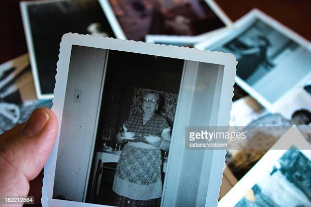 Hand holds Vintage photograph of 1950s grandma serving soup