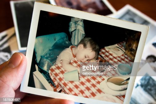 Hand holds Vintage photograph of boy at thanksgiving