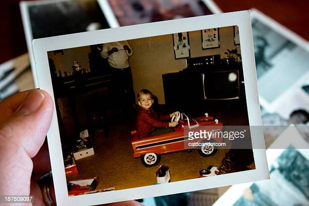Hand holds Vintage photograph of boy in pedal car