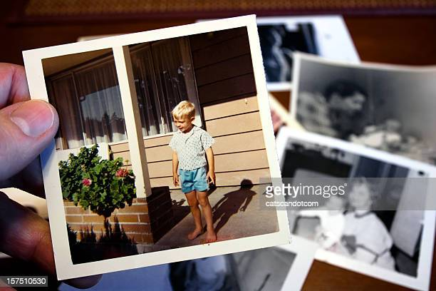 Hand holds Vintage photograph of child during summer