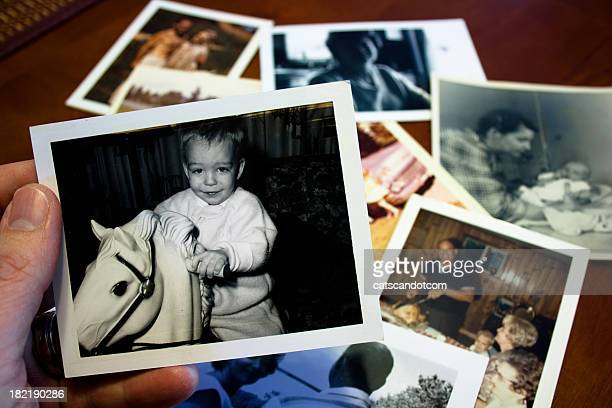 Hand holds Vintage photograph of child with hobby horse toy