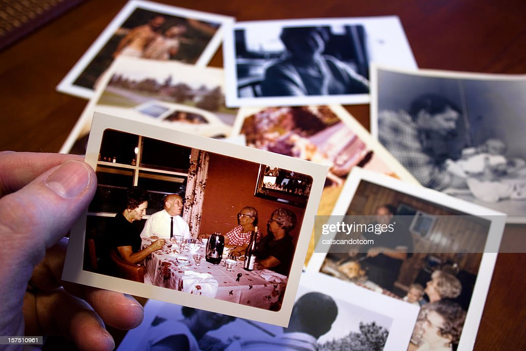 Hand holds Vintage photograph of parents and grandparent couple : Stock Photo