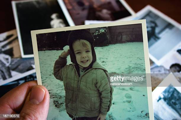 Hand holds Vintage photograph with boy in snow