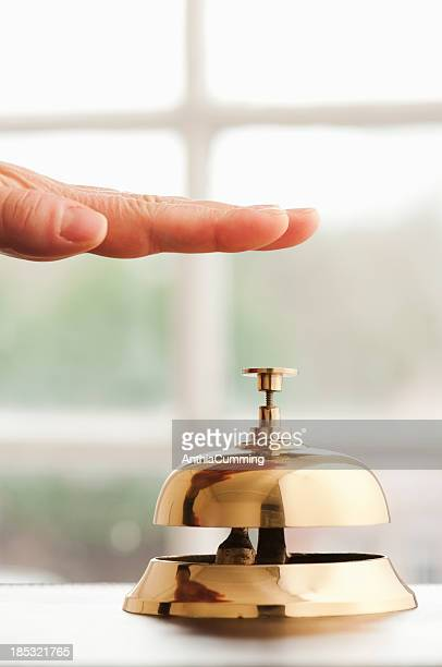 Hand hovering over service bell on desk beside window