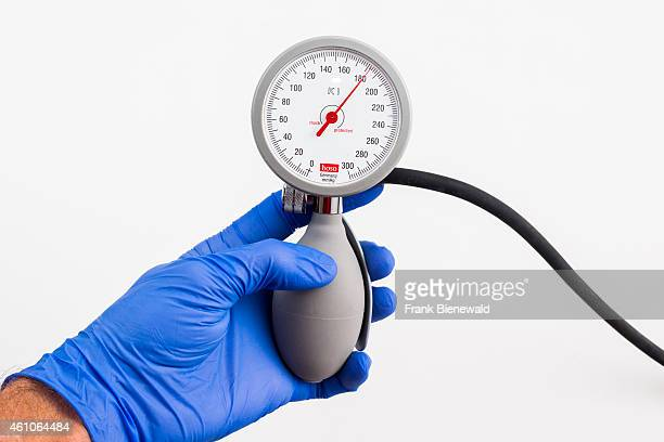A hand in a blue medical glove is holding a sphygomanometer blood pressure meter for medical use indicating high blood pressure displayed on a white...