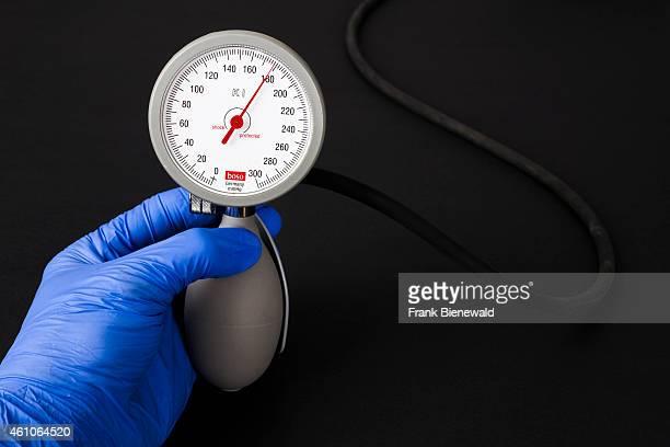 A hand in a blue medical glove is holding a sphygomanometer blood pressure meter for medical use indicating high blood pressure displayed on a black...