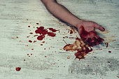 Hand in blood on a white floor. Concept photo of murder and crime. young man's body on the floor with bloody wounds and blood on his arm and close a folding knife with drops of blood. Suicide.