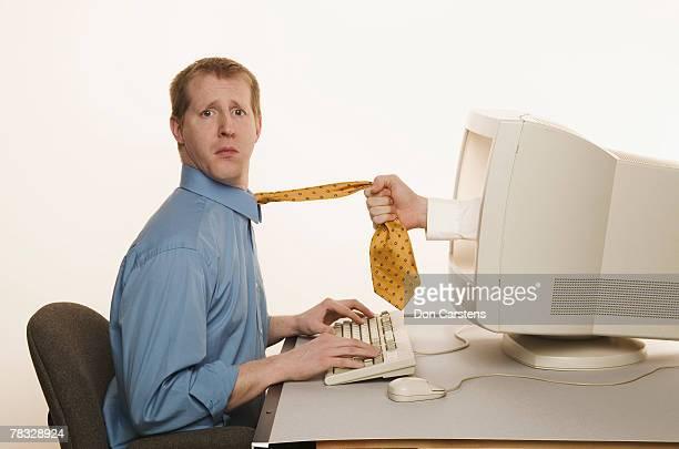 Hand in computer grabbing man's tie