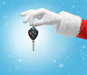 Hand in costume Santa Claus is holding car keys / studio shot of man's hand holding keys / Merry Christmas & New Year's Eve concept / Closeup on blurred blue background.