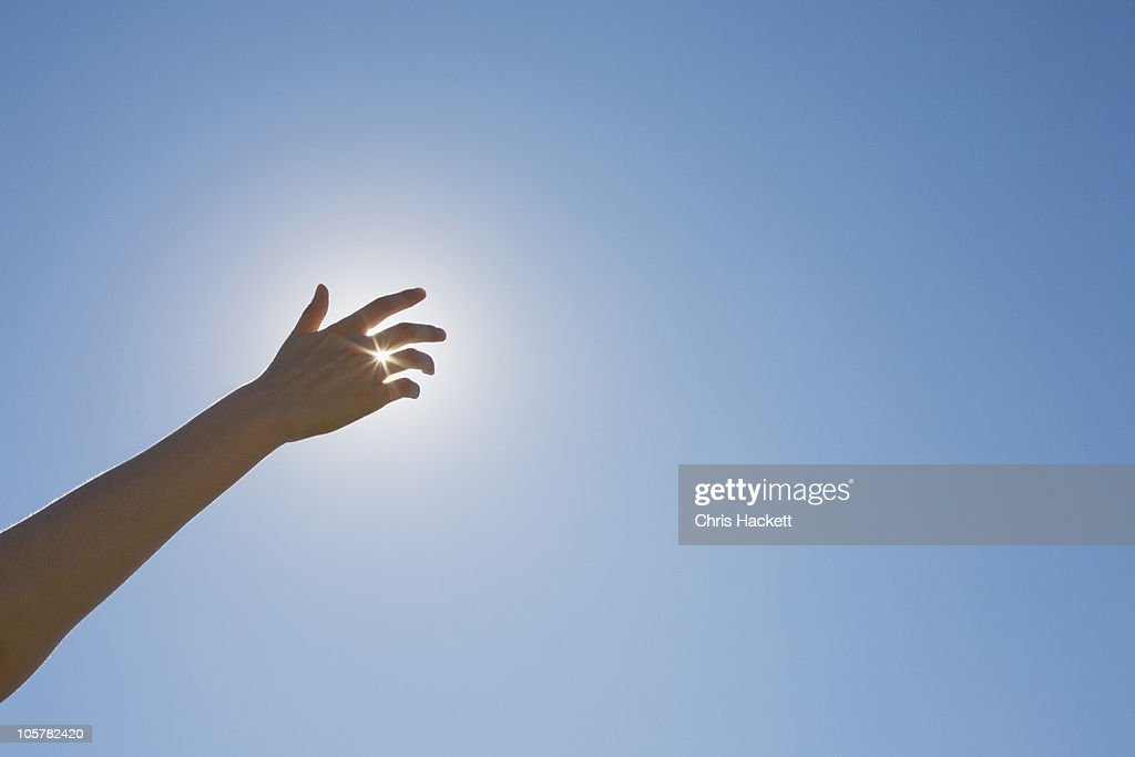 Hand in front of a sun flare in the sky : Stock Photo