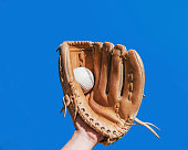 Hand in glove for a baseball game caught a leather white ball on a blue sky background. Sports contests. Victory. Achievement of success.