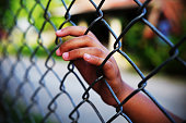 Hand in jail with girl and house of detention concept, vignette effect and selective focus.