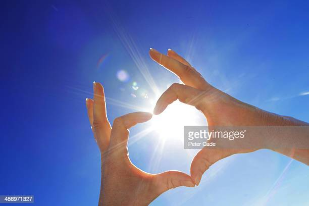 Hand in shape of heart held up to sun