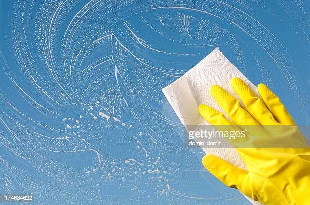 Hand in yellow protective glove is cleaning window, sky background
