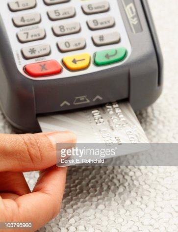 Hand inserting credit card into machine : Foto stock