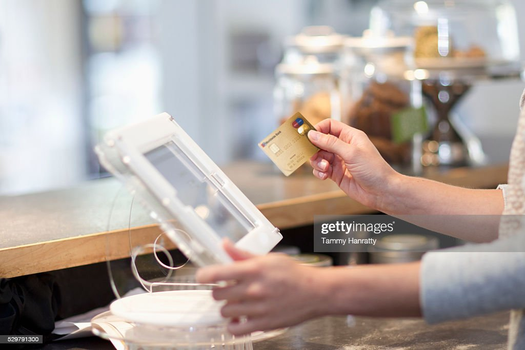 Hand inserting credit card into reader : Stock Photo