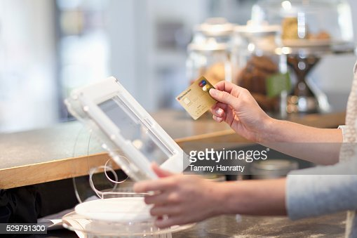 Hand inserting credit card into reader : Stockfoto