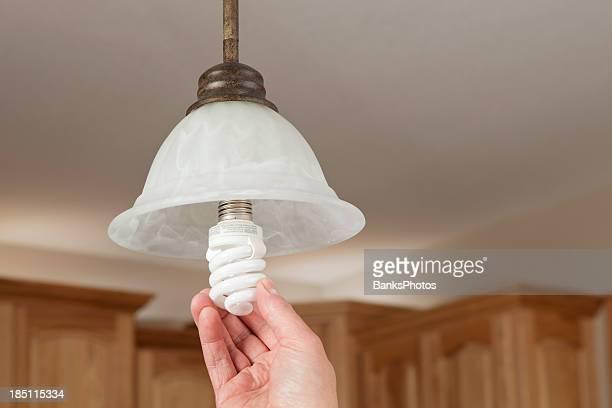 Manos instalar lámpara las fluorescentes compactas de luz