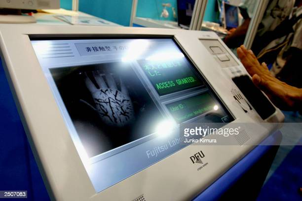 A hand is placed above the prototype of Fujitsu's new biometric authentication device which can identify a person by reading the veins without the...