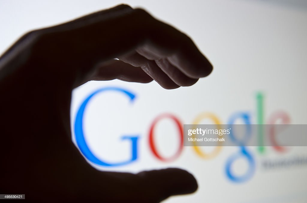 A hand is seen in front of a screen on which the Google search engine is displayed on June 02, 2014 in Berlin, Germany.