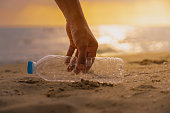 Hand Keep  cleanup  the Plastic bottle on beach at the sunset scene