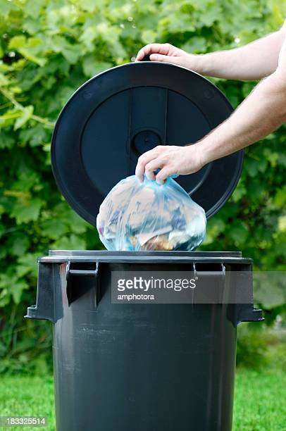 Hand lifting a garbage bin lid, another hand disposes trash