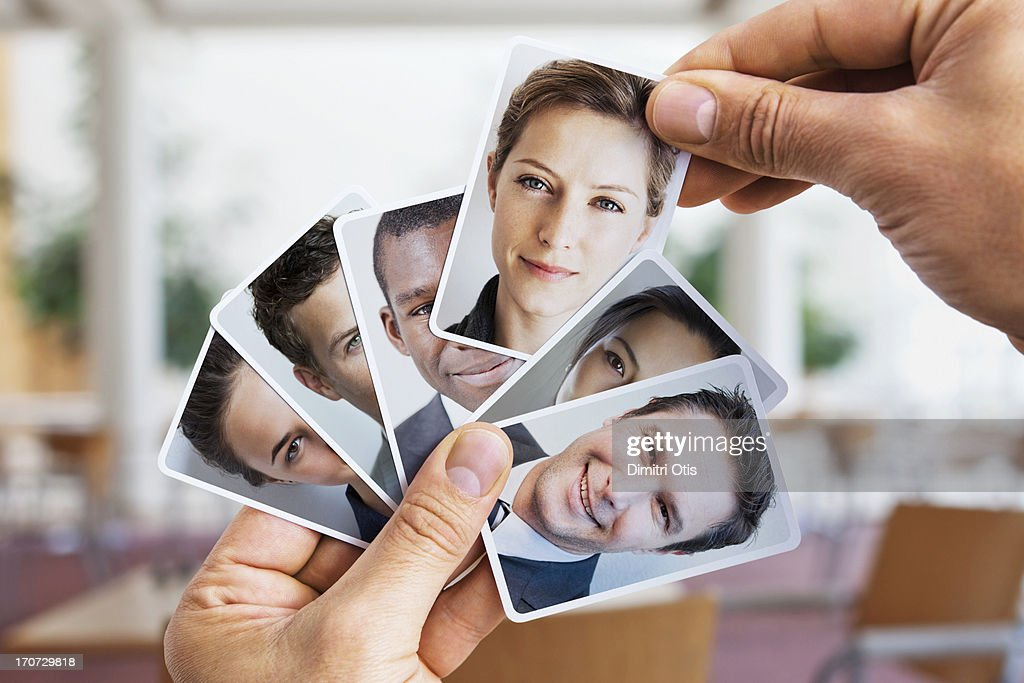 Hand lifting portrait card out from others