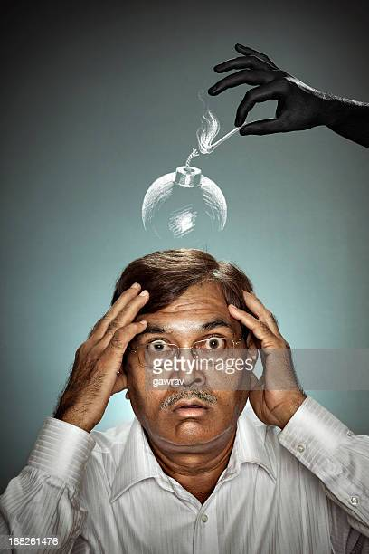 Hand lighting bomb above the head of shocked mature man.