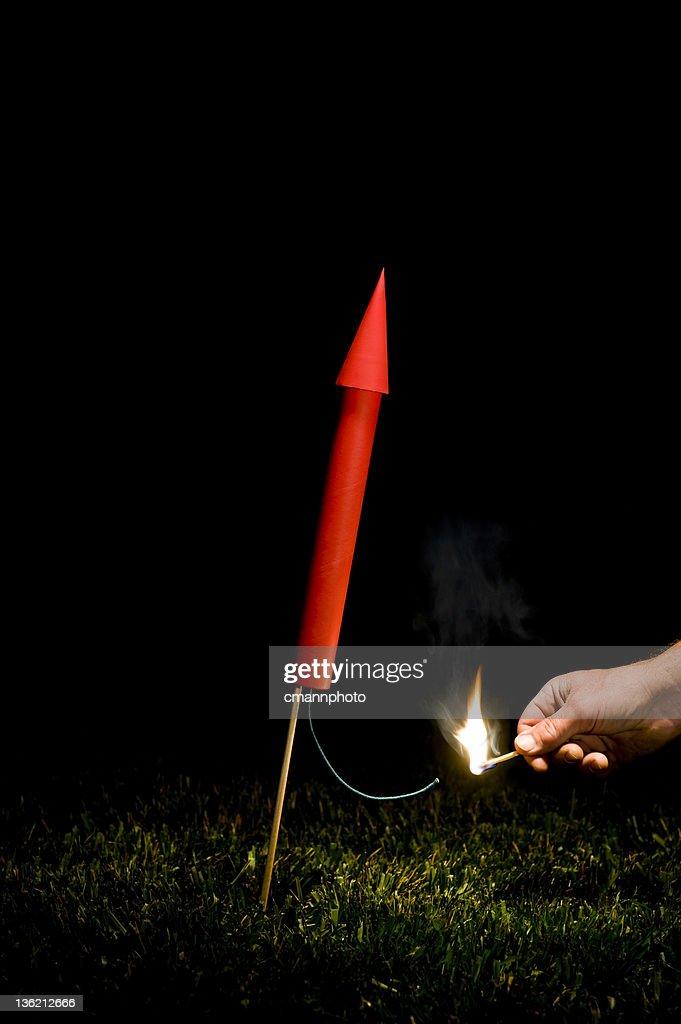 Hand lighting red Rocket/Fireworks fuse