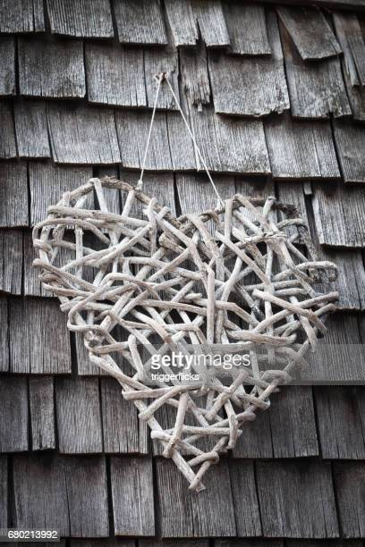 A hand made heart of straw on a wall with shingles