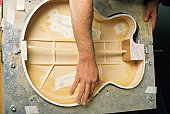 Hand Manufacturing wooden guitar in factory