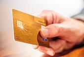 Nahaufnahme einer Hand mit einer goldenen Kreditkarte