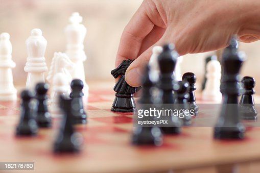 Hand moving a Knight piece on a chessboard