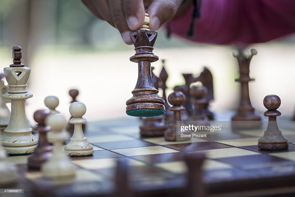 Hand moving chess piece on board, close up