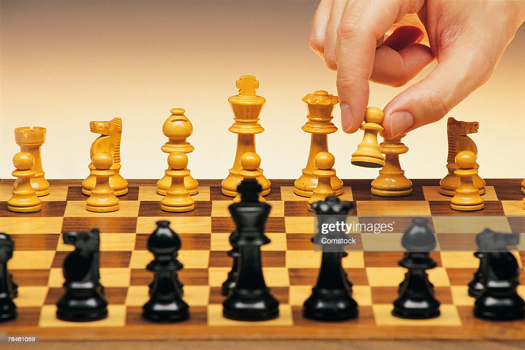 Hand moving piece on chessboard : Stock Photo