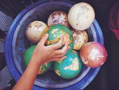 Hand of a child reaching for a small world globe