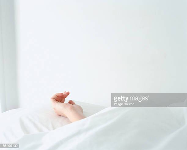 Hand of a female resting on a pillow