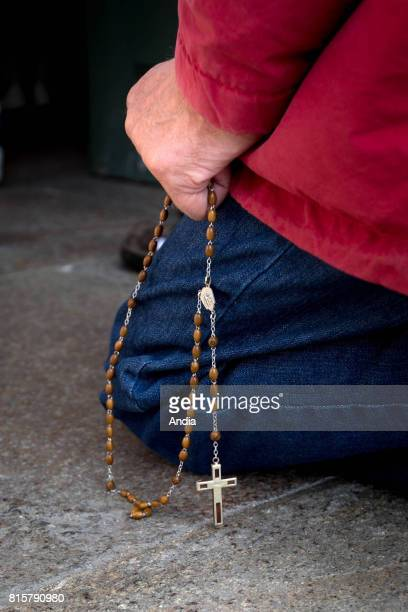 Hand of a kneeling man holding a rosary