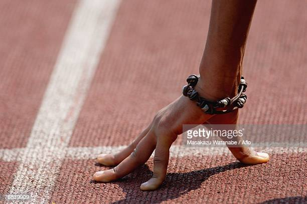 Hand of a Male Runner Pressed Against the Surface of a Track