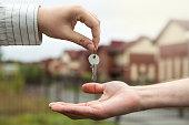 hand of a man handing keys to a man's hand