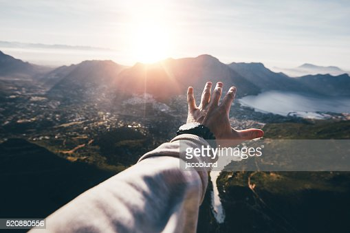 Hand of a man reaching out the beautiful landscape : Stock Photo