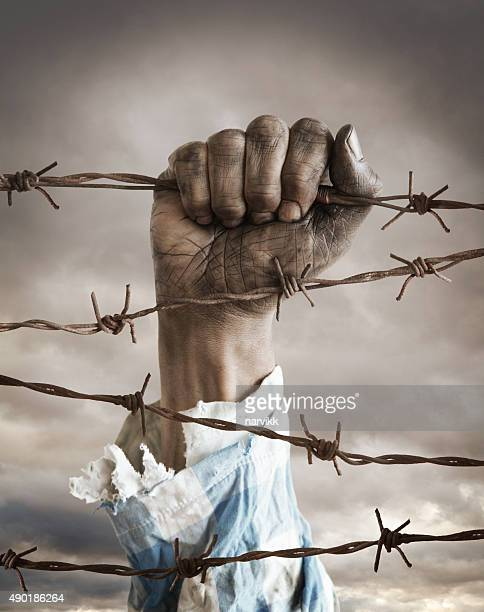 Hand of a refugee behind barbed wire