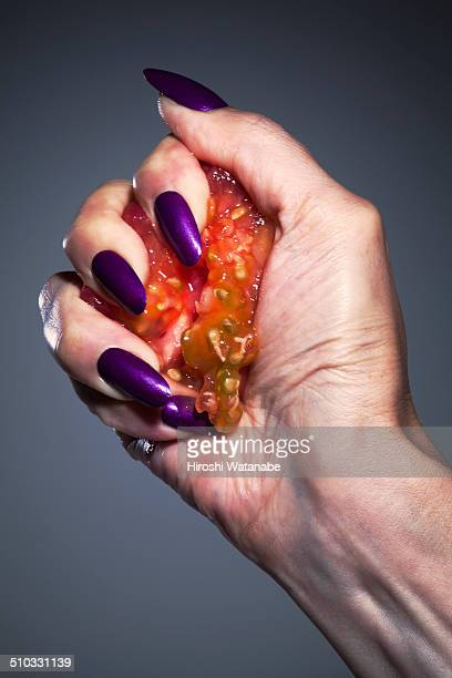 Hand of a woman crushing tomato