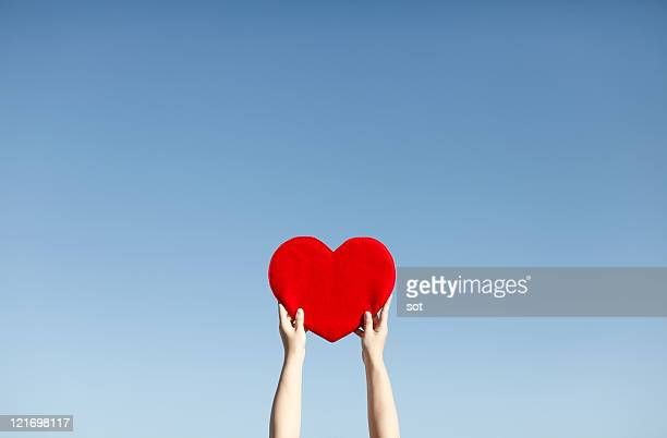 Hand of a woman lifting red heart,against blue sky